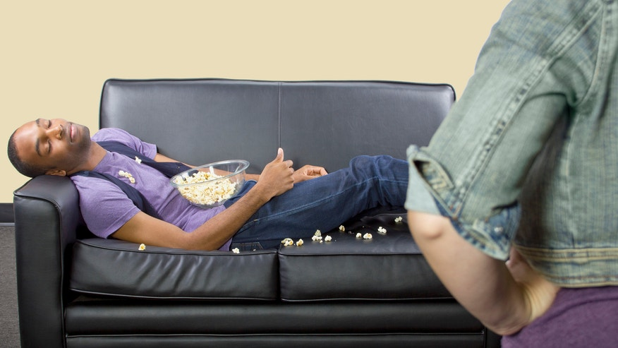 Teenage boy napping on a leather couch, spilling popcorn