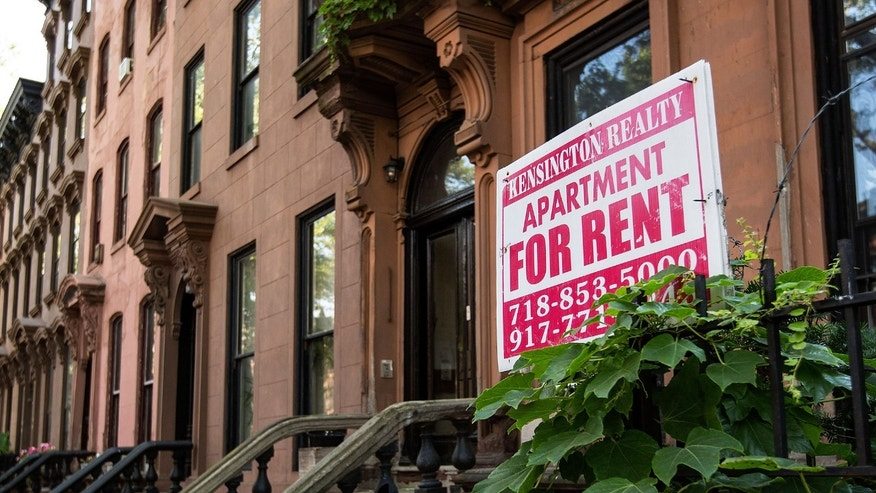 A sign advertises an apartment for rent along a row of brownstone townhouses in the Fort Greene neighborhood of Brooklyn.