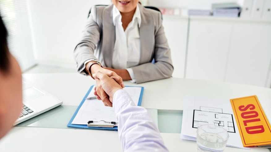 real estate agent shaking hands; what is a buyer's agent?