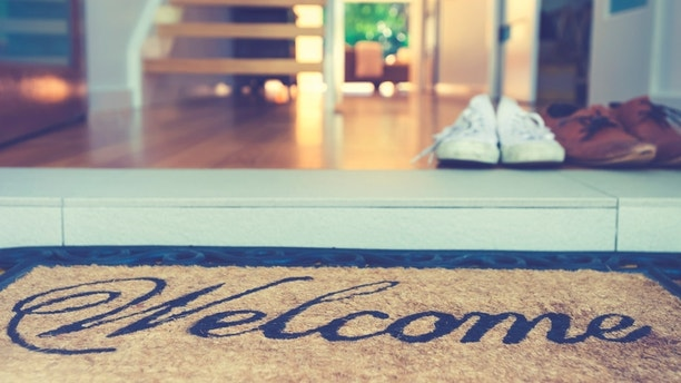 Couples shoes at the front door of a house. There is a welcome mat in the foreground, with a modern home interior in the background. Marriage - home ownership concept