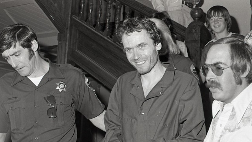 In this 1977 photo serial killer Ted Bundy, center, is escorted out of court in Pitkin County, Colo.