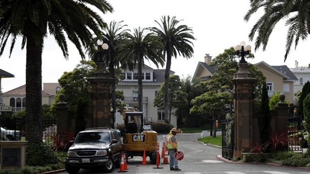 """A construction workers stands in front of a gate leading into the Presidio Terrace neighborhood Monday, Aug. 7, 2017, in San Francisco. Thanks to a city auction stemming from an unpaid tax bill, a Bay Area real state investor bought the street in the neighborhood and now owns the sidewalks, the street itself and other areas of """"common ground"""" in the private development that, the San Francisco Chronicle reports, has been managed by the homeowners association since at least 1905. (AP Photo/Marcio Jose Sanchez)"""