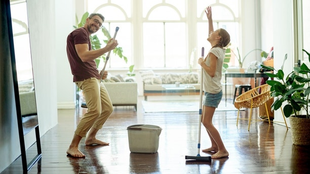 Shot of a handsome mature man and his daughter mopping the floors in their home as part of their spring cleaning