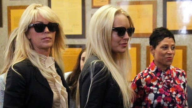 Actress Lindsay Lohan (C) stands with her mother Dina Lohan (L) and attorney Shawn Chapman Holley (R) as she waits to go through the metal detector at the Beverly Hills Municipal Courthouse July 20, 2010, where she is due to surrender for a 90-day jail sentence for violating the terms of her probation on drunk driving charges by missing alcohol education classes in Beverly Hills, California. REUTERS/Danny Moloshok (UNITED STATES - Tags: ENTERTAINMENT CRIME LAW) - GM1E67L00L001