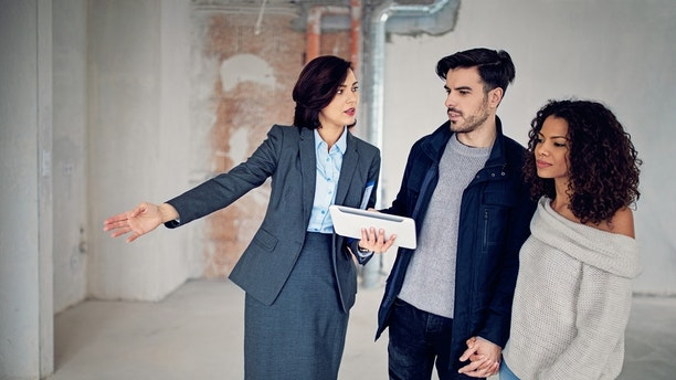 Real estate agent is showing new apartment to a young couple