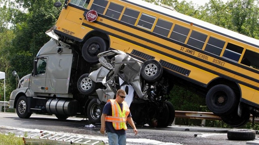 Aug. 5, 2010: A rescue worker is seen at the scene of an accident involving two school buses, a tractor-trailer and another passenger vehicle, near Gray Summit, Mo. Federal safety investigators say a 19-year-old driver was texting at the time his pickup truck, two school buses and other vehicles collided in a deadly pileup on an interstate highway in Missouri last year.