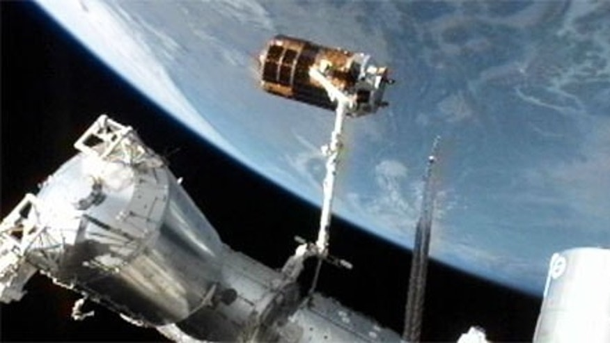 Japan's unmanned HTV-3 cargo ship is perched at the end of the International Space Station's robotic arm before its release on Sept. 12, 2012, to end its delivery mission to the orbiting lab.