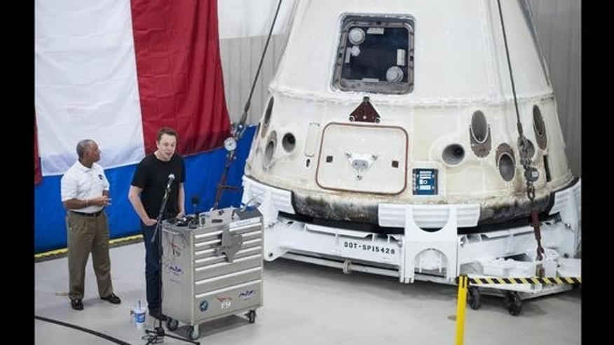 NASA Administrator Charles Bolden (left) and SpaceX CEO Elon Musk view the historic Dragon capsule that returned to Earth on May 31 following the first successful mission by a private company to carry supplies to the International Space Station
