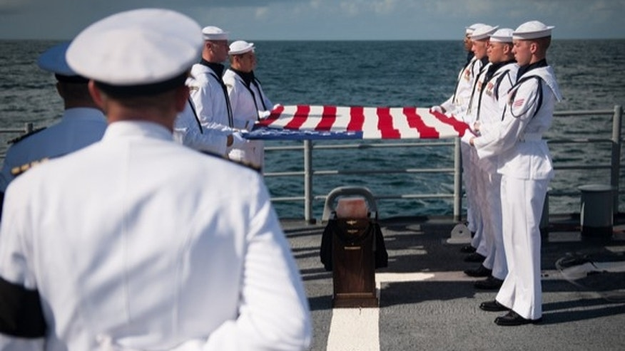 Members of the US Navy ceremonial guard hold an American flag over the cremains of Neil Armstrong,  Apollo 11 commander and the first person to walk on the moon, during a burial at sea service aboard the USS Philippine Sea (CG 58), Friday, Sept