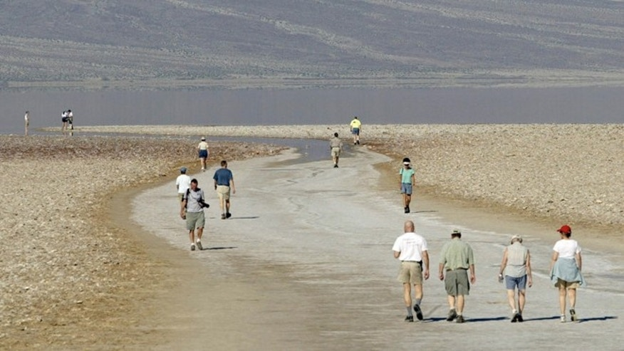March 10, 2005: Tourists walk down to the edge of the Badwater Basin, the lowest elevation in the United States, 282 ft below sea level, with the Panamit Range in the background at Death Valley National Park, Calif.