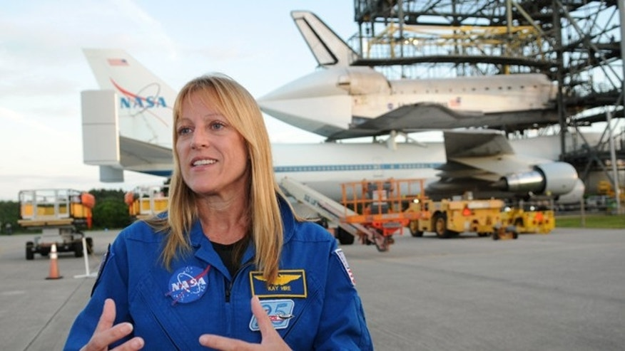"Sept. 16, 2012: Astronaut Kathryn ""Kay"" Hire, a captain with the U.S. Navy who has logged  over 711 hours in space, speaks to reporters as the space shuttle Endeavour is prepared for transport on a modified Boeing 747 aircraft at the Kennedy Space Center in Cape Canaveral, Fla."
