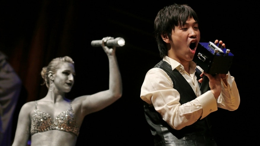 "Sept. 20, 2012: Koji Tsukada yells into his invention the ""SpeechJammer"" during a performance at the Ig Nobel Prize ceremony at Harvard University, in Cambridge, Mass."