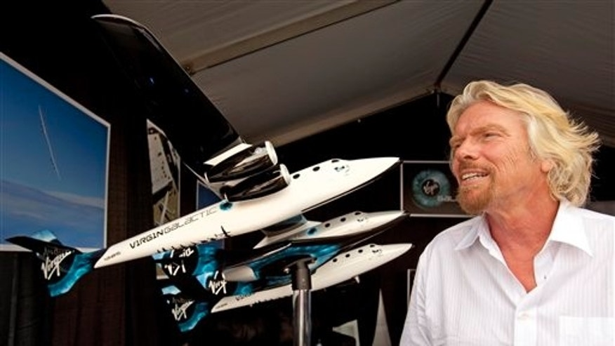 July 27, 2009: With a model of WhiteKnightTwo behind him, Sir Richard Branson gives an interview at the Experimental Aircraft Association's annual AirVenture convention in Oshkosh, Wis.