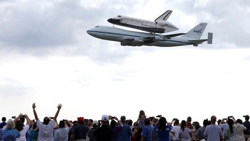 Sept. 19, 2012: Space shuttle Endeavour flies over Ellington Field in Houston atop the shuttle aircraft carrier Wednesday.