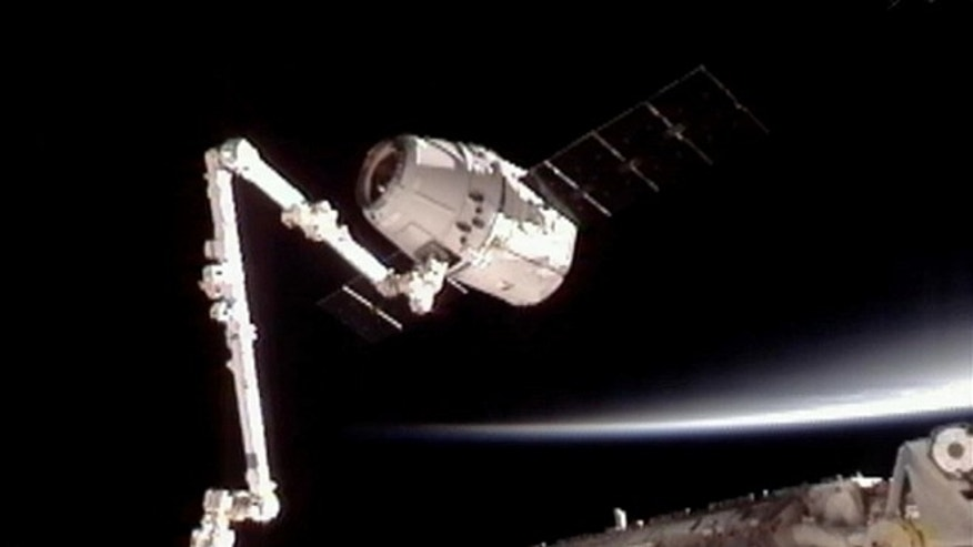May 25, 2012: NASA-TV shows the SpaceX Dragon commercial cargo craft, top, after Dragon was grappled by the Canadarm2 robotic arm and connected to the International Space Station. Dragon is scheduled to spend about a week docked with the station before returning to Earth on May 31 for retrieval.