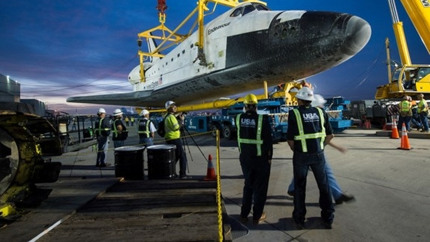 The overland transporter is moved into position below the space shuttle Endeavour not long after the orbiter was demated from the NASA 747 Shuttle Carrier Aircraft (SCA) during the early morning hours on Saturday, Sept. 22, 2012, at Los Angeles