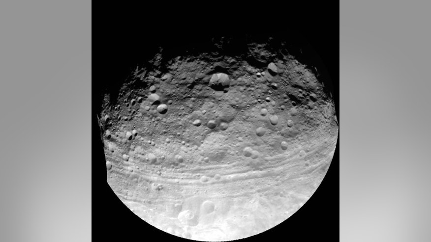 An image taken by NASA's Dawn spacecraft on July 24, 2011, shows troughs along the equator of the asteroid Vesta, including Divalia Fossa, which is larger than the Grand Canyon. A new study analyzing these troughs finds that they are probably g