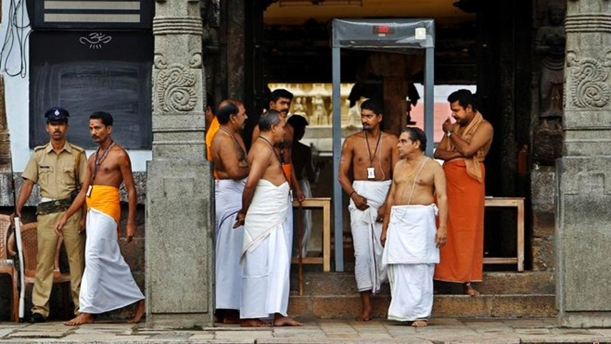 July 6, 2011: A policeman stands guard as temple staff crowd at the north side entrance of the 16th century Sree Padmanabhaswamy temple. Small groups of armed policemen patrol the temple grounds in the heart of the Kerala state capital.
