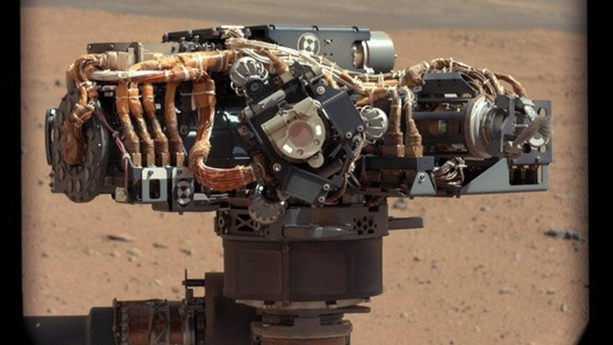 This image shows the Mars Hand Lens Imager (MAHLI) on NASA's Curiosity rover, with the Martian landscape in the background. The image was taken by Curiosity's Mast Camera on the 32nd Martian day, or sol, of operations on the surface (Sept. 7, 2