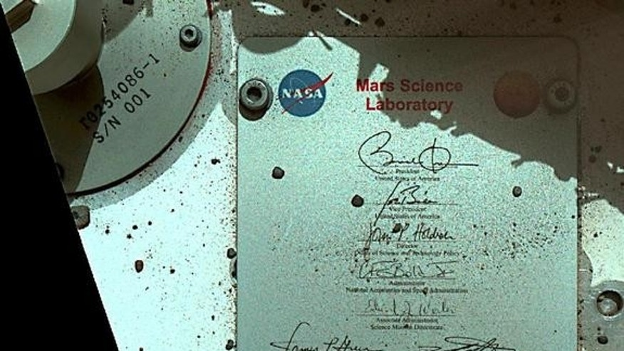 This view of Curiosity's deck shows a plaque bearing several signatures of US officials, including that of President Obama and Vice President Biden. The image was taken by the rover's Mars Hand Lens Imager (MAHLI) during the rover's 44th Martia