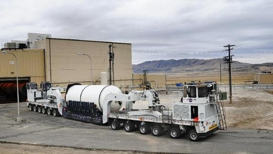 The forward segment of the qualification motor for NASA'S Space Launch System rocket is transported through manufacturing and assembly at ATK's facility in Promontory, Utah in preparation for a full-scale ground test there in the spring of 2013