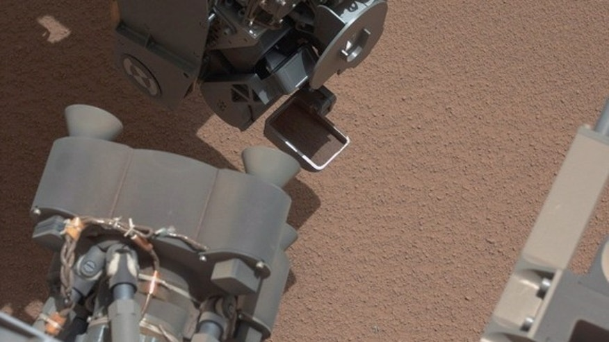 This image from the right Mast Camera (Mastcam) of NASA's Mars rover Curiosity shows a scoop full of sand and dust lifted by the rover's first use of the scoop on its robotic arm. In the foreground, near the bottom of the image, a bright object