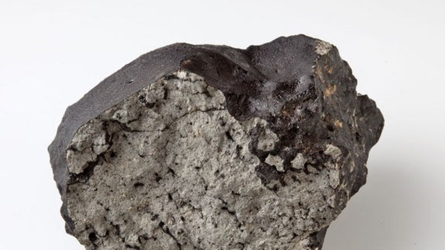 The 1.1 kg stone of the Tissint Martian meteorite at the Natural History Museum, London. The stone has a glossy black fusion crust. The fresh interior shows the large yellow/green olivine macrocrysts and pockets of black glass which are charact