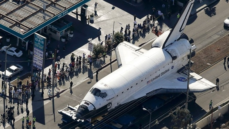 Oct. 12, 2012: Spectators gather to watch the space shuttle Endeavour make its way down Manchester Blvd. on a 160-wheeled carrier in Los Angeles.