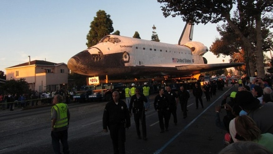 The rising sun bathes space shuttle Endeavour in a golden glow as it rolls down Martin Luther King Jr. Boulevard on Oct. 14, 2012.