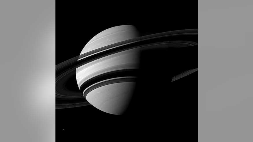 NASA's Cassini spacecraft snapped this angled shot of Saturn, showing the southern reaches of the planet with the rings on a dramatic diagonal. Saturn's icy moon Enceladus is visible as a tiny white speck in the lower lefthand corner. The pictu