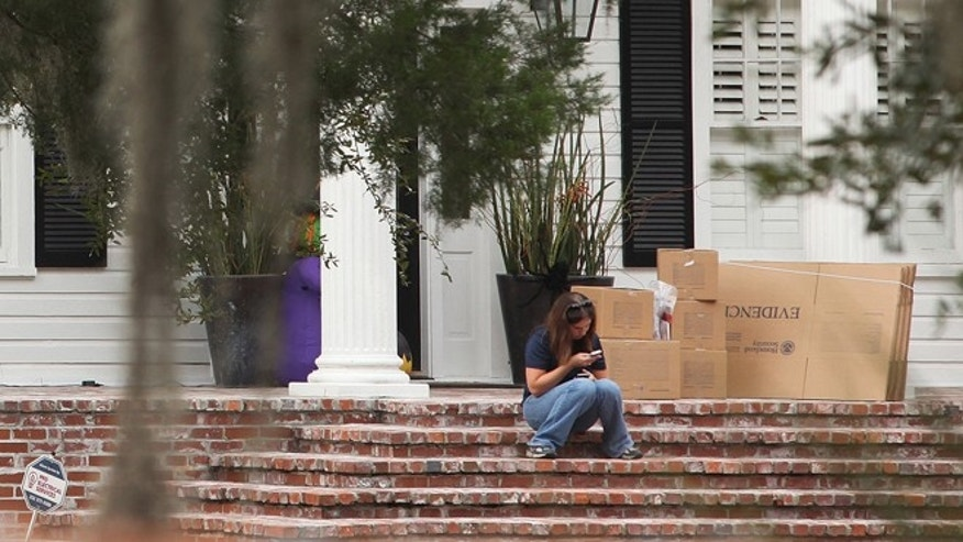 "Oct. 17, 2012: A woman uses her cell phone near evidence boxes as agents with the Department of Homeland Security collect evidence at the home of Eric Prokopi, a self-described ""commercial paleontologist,"" in Gainesville, Fla."