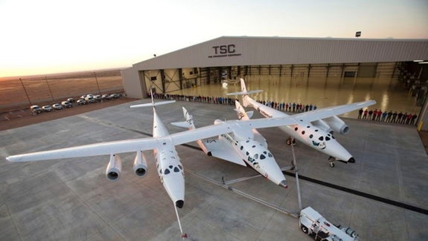 """Virgin Galactic's first SpaceShipTwo suborbital spaceliner (center) is seen mated to its WhiteKnightTwo mothership in front of the """"Faith"""" hangar at The Spaceship Company during a dedication ceremony in Mojave, Calif."""