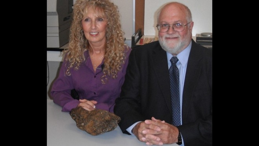 Donna Lewis, left, with Dr. Jerry Cook and the meteorite.