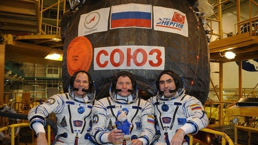 The three members of Expedition 33 pose wearing their spacesuits in front of the Soyuz capsule that will transport them to the International Space Station. L to R:  American astronaut Kevin Ford (of NASA), Soyuz Commander Oleg Novitskiy, Flight