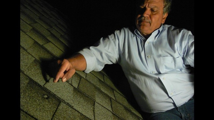 The dent in a roof caused by a meteorite from the Oct. 17, 2012, fireball over Northern California is identified by Luis Rivera, the neighbor of Lisa Webber who found the object.
