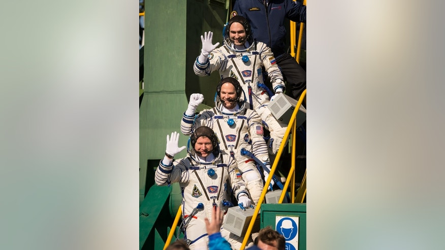 Expedition 33/34 crew members, Soyuz Commander Oleg Novitskiy, bottom, Flight Engineer Kevin Ford of NASA, and Flight Engineer Evgeny Tarelkin of ROSCOSMOS, top, wave farewell before boarding their Soyuz rocket just a few hours before their lau