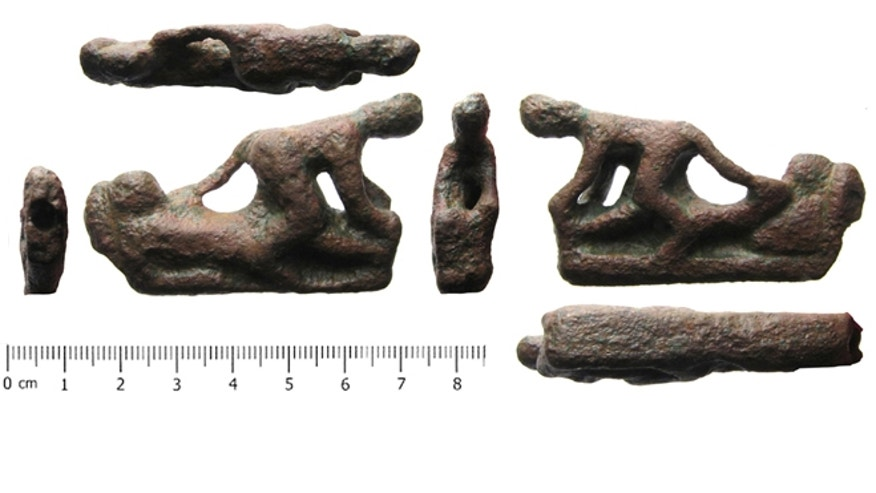 This copper alloy knife handle shows a couple having sex.