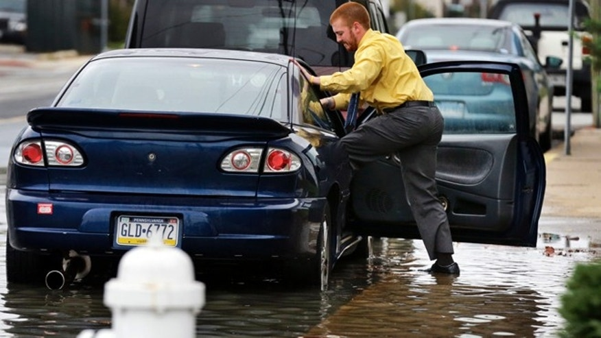 Oct. 28, 2012: Cody Billotte walks through the high water as he loads his car to go to work as Hurricane Sandy bears down on the East Coast in Ocean City, Md.