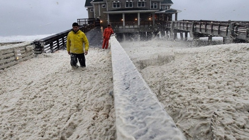 Oct. 28, 2012: A news crew wades through sea foam blown onto Jeanette's Pier in Nags Head, N.C., as wind and rain from Hurricane Sandy move into the area.