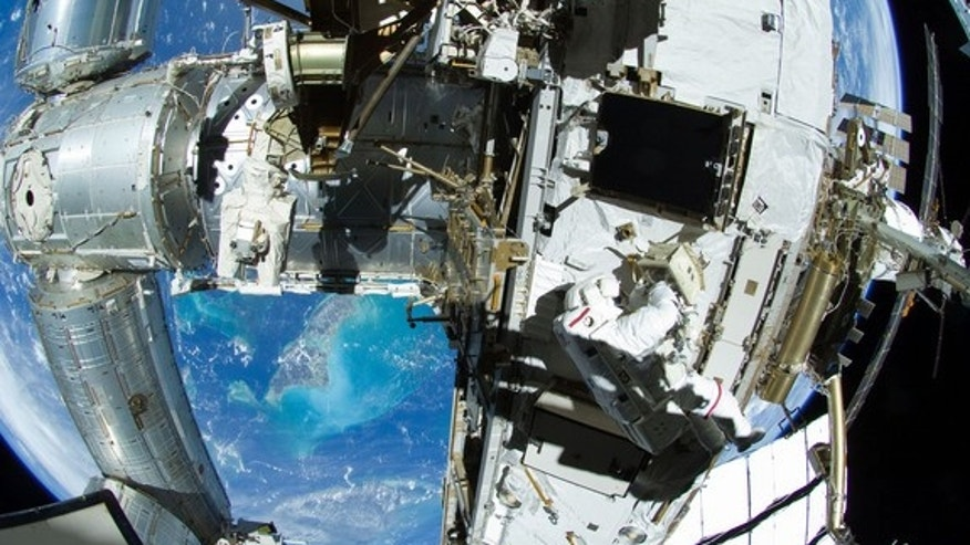 With the Andros Island and other parts of the Bahamas in the backdrop, NASA astronaut Sunita Williams and Japanese astronaut Akihiko Hoshide (out of frame) work on the exterior of the International Space Station during an Aug. 30, 2012 spacewal