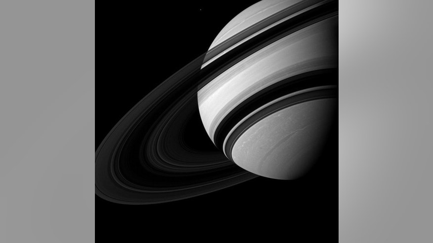 Saturn's moon Mimas appears near Saturn, dwarfed by its parent planet in this image.  Mimas (246 miles, or 396 kilometers across) appears tiny compared to the storms clearly visible in far northern and southern hemispheres of Saturn. The image