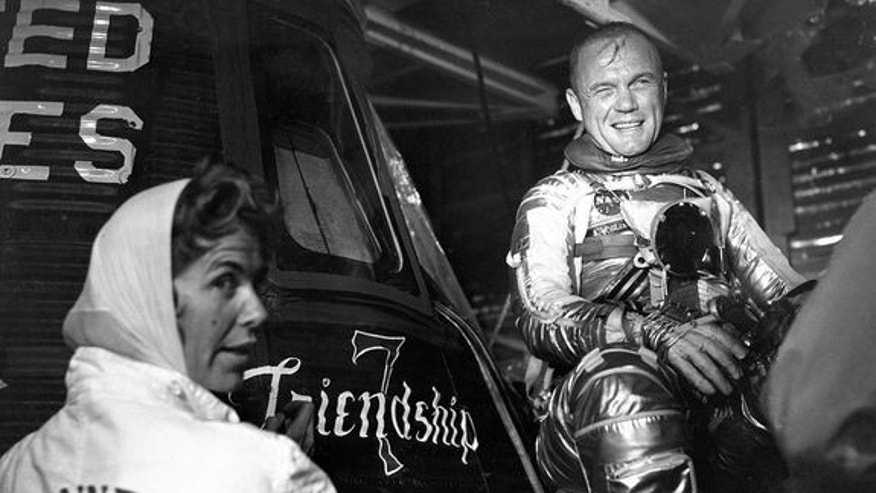 Artist Cece Bibby (at left) puts the final touches on the Friendship 7 logo as astronaut John Glenn looks on in approval.