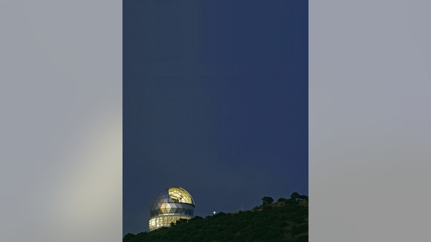 The Hobby-Eberly Telescope at the McDonald Observatory in Austin Texas gleams in silver and gold against a deep blue night sky.