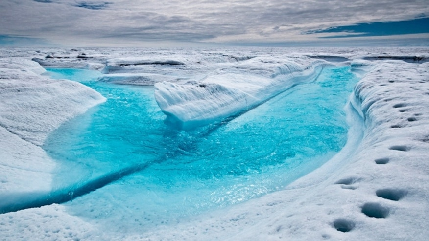 A stream of meltwater flows across the ice surface in Greenland.