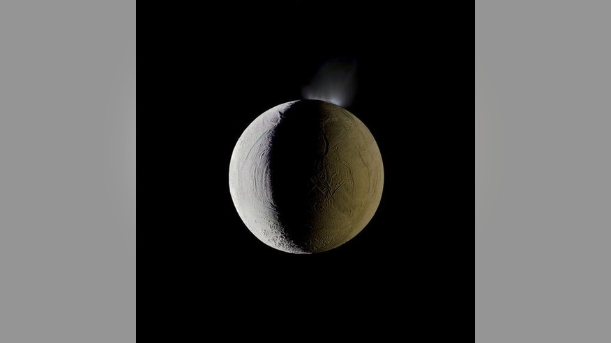 Enceladus vents water into space from its south polar region. The moon is lit by the Sun on the left, and backlit by the vast reflecting surface of its parent planet to the right. Icy crystals from these plumes are likely the source of Saturn's