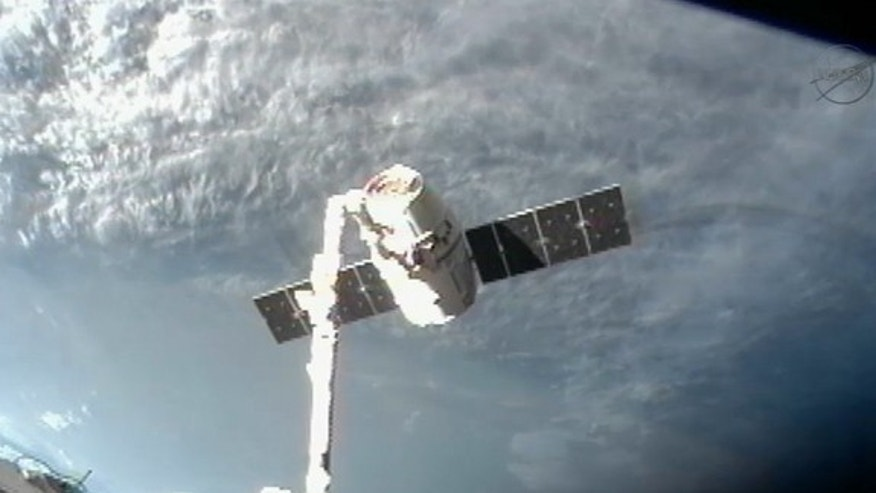 The private Dragon capsule built by SpaceX is seen at the end of the International Space Station's robotic arm during its undocking on Oct. 28, 2012, in this camera view. The Dragon capsule made the first commercial cargo delivery to the space