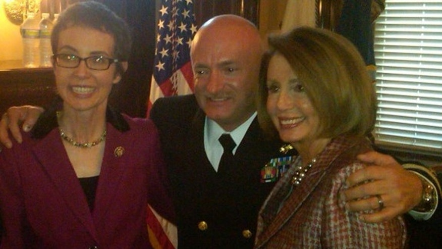 Nancy Pelosi poses wiith Rep. Giffords at Captain Mark Kelly's military retirement ceremony.