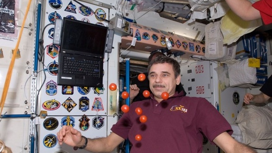 Russian cosmonaut Mikhail Kornienko, Expedition 23 flight engineer, is pictured near fresh tomatoes floating freely in the Unity node of the International Space Station in May 2010.
