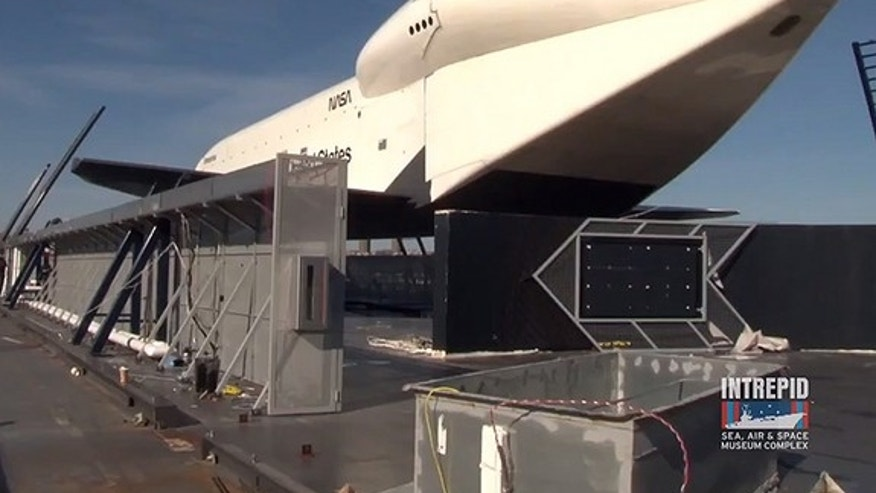 Space shuttle Enterprise, seen here with the original remnants of its Hurricane Sandy-damaged display, will be temporarily covered for the winter.
