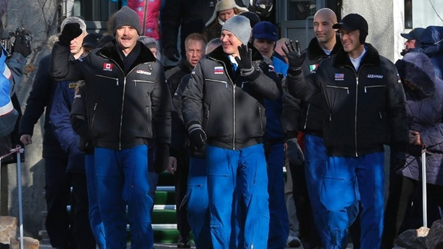 Dec. 19, 2012: U.S. astronaut Thomas Marshburn, right, Russian cosmonaut Roman Romanenko, center, and Canadian astronaut Chris Hadfield, crew members of the mission to the International Space Station, ISS, walk to a bus from a hotel prior the launch of Soyuz-FG  rocket at the Russian leased Baikonur cosmodrome, Kazakhstan.